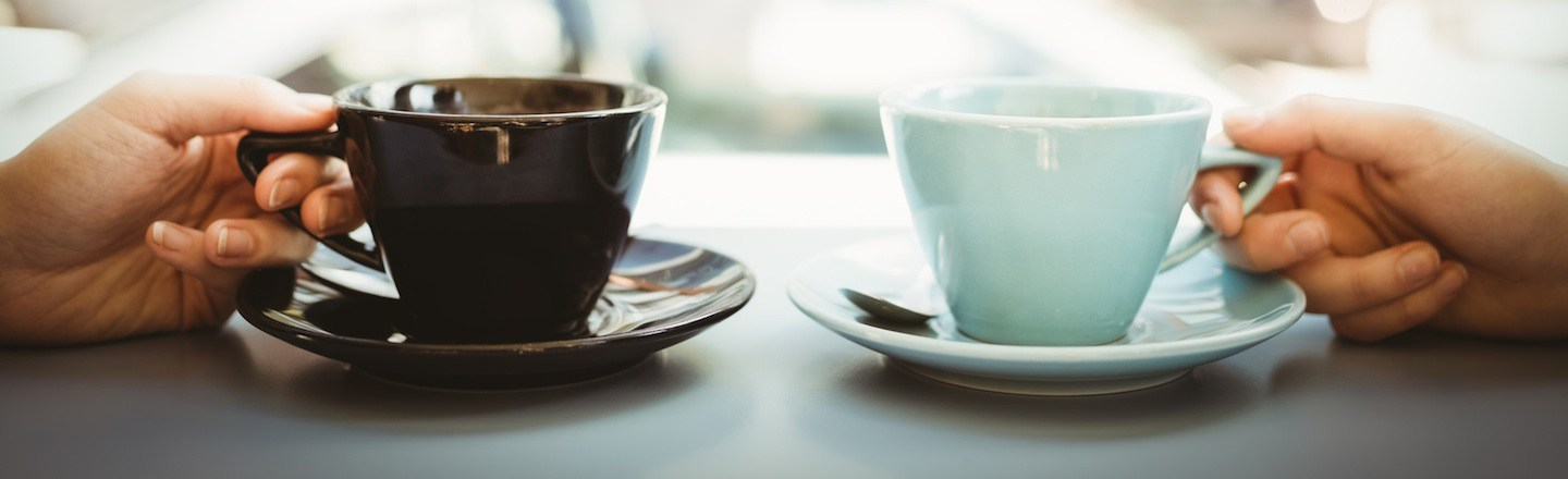 Close up photo of two people holding coffee mugs